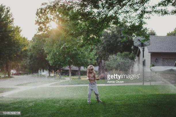 Boy getting sprayed by lawn sprinkler