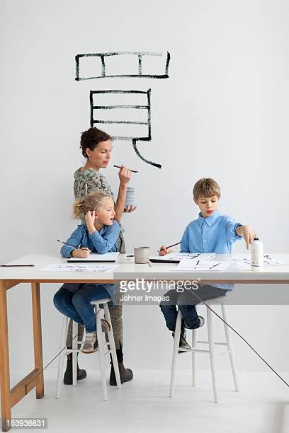 Boy, girl and female teacher caligraphing chinese signs
