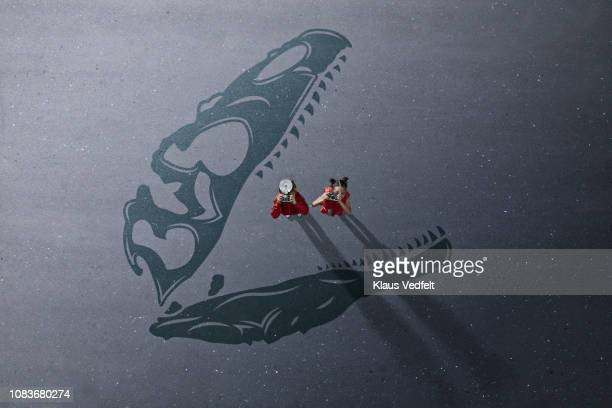 Boy & girl standing on shadow of dinosaur with cameras and looking up