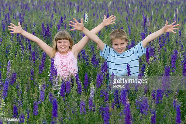 Boy & Girl Waving In A Filed Of Flowers