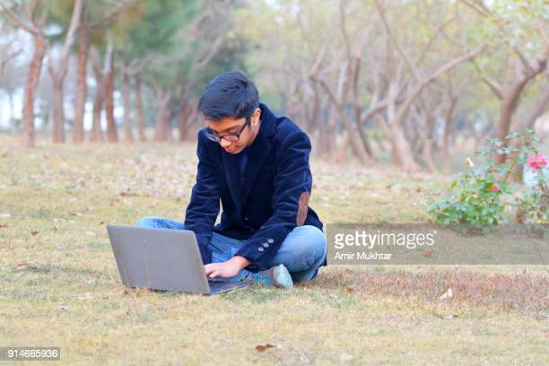 a boy girl working on laptop in the garden - amir mukhtar stock photos and pictures