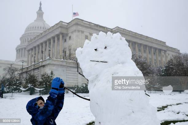 A boy gives a snow man stick arms in front of the US Capitol March 21 2018 in Washington DC An early spring storm brought several inches of snow to...