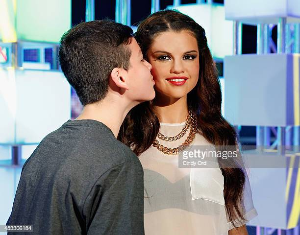 A boy gives Madame Tussauds wax figure of Selena Gomez a kiss as Madame Tussauds New York unveils new neverbeforeseen Selena Gomez wax figure at...