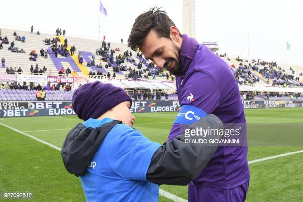 A boy gives the captain's armband to Fiorentina's player Davide Astori on February 25 2018 before the Italian Seria A football match Fiorentina vs...