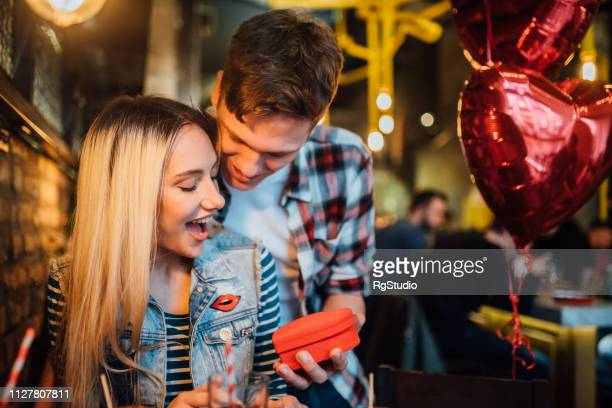 boy giving a gift to his girlfriend - valentines day dinner stock pictures, royalty-free photos & images