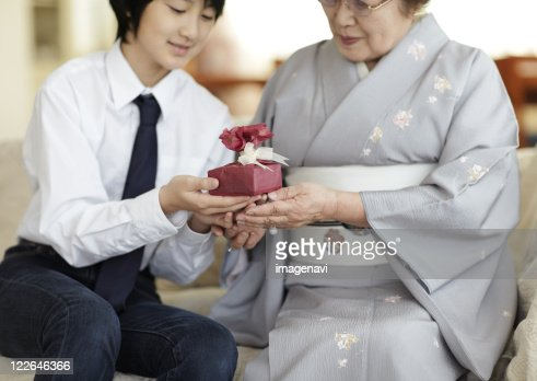 Boy giving a gift to his grandmother