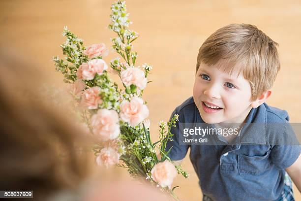 boy giving bouquet flowers to mother - muttertag blumen stock-fotos und bilder