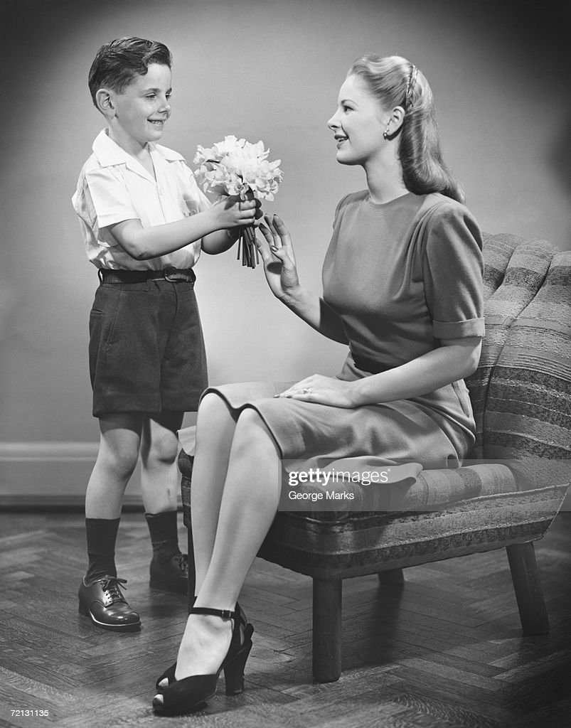 Boy (8-9) giving bunch of flowers to mother (B&W) : Stockfoto