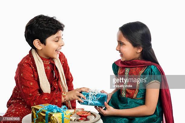 Boy giving gift to his sister at Raksha Bhandan