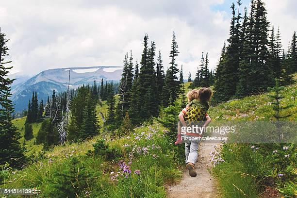 Boy (4-5) giving girl (2-3) piggyback ride along mountain trail