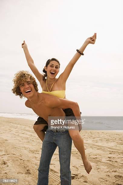 Boy giving girl piggyback ride on beach