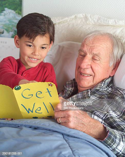 Boy (4-6) giving grandfather 'Get Well' card, smiling