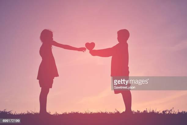 Boy Giving Heart Shape To Girl Against Sky During Sunset