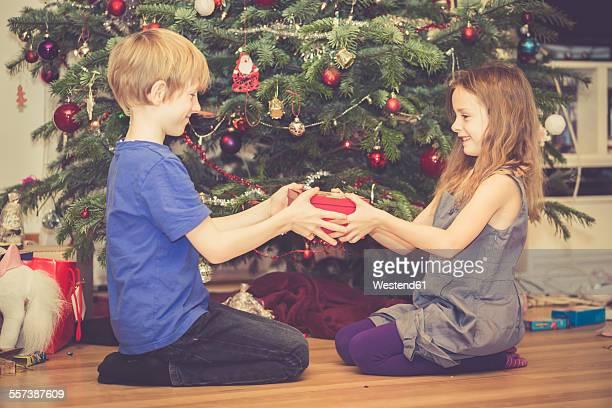 Boy giving his little sister Christmas present