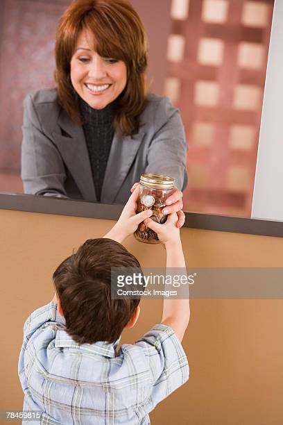 boy giving jar of change to bank teller - 40 44 jaar stock pictures, royalty-free photos & images