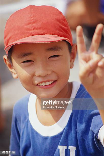 Boy giving peace sign
