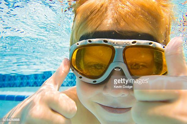 Boy Giving Thumbs Up Sign in Swimming Pool
