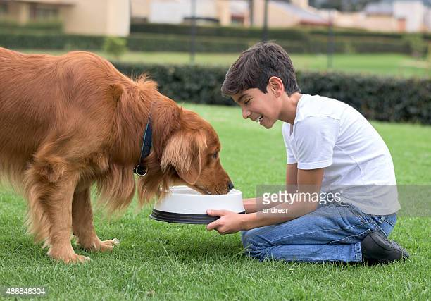 Boy giving water to his dog