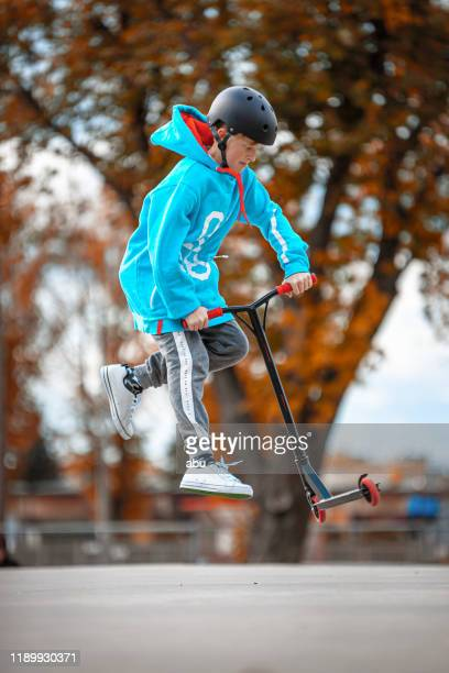 boy going airborne with a scooter - stunt stock pictures, royalty-free photos & images