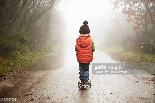 Boy going down path on scooter in winter