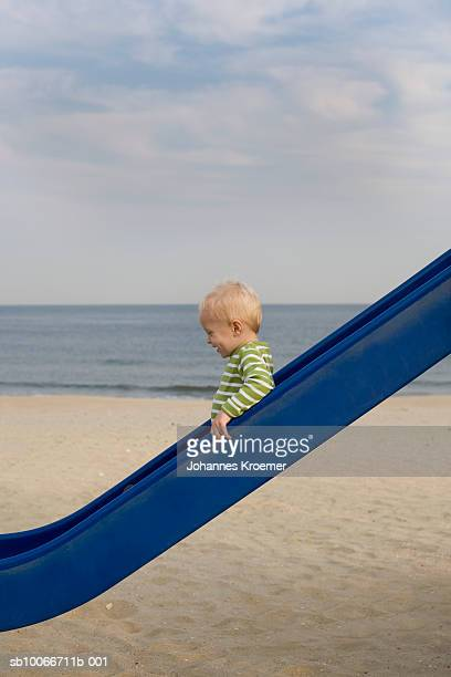 boy (18-23 months) going down slide on beach, side view - 滑る ストックフォトと画像
