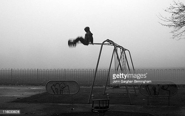 Boy Going High On Swing In Park