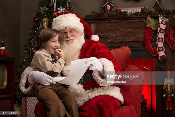 boy going over naughty nice list with santa - naughty santa stock photos and pictures
