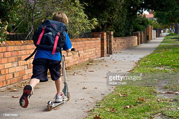 boy going to school on scooter