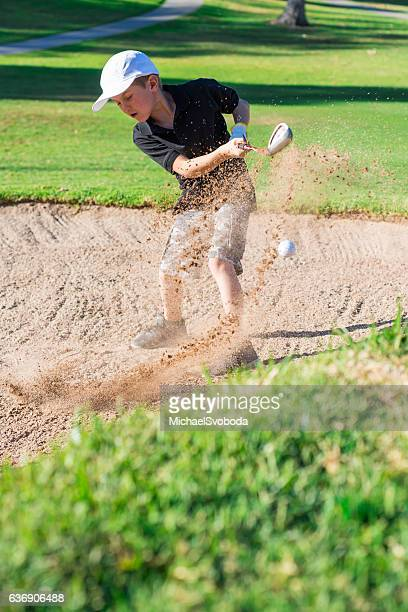 boy golfer hitting out a sand bunker - junior level stock pictures, royalty-free photos & images
