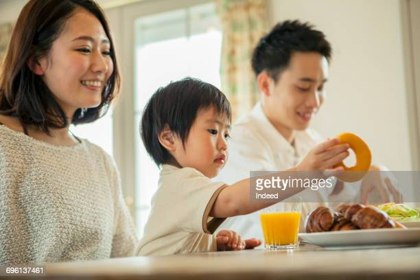 Boy grabbing donut with parents on table