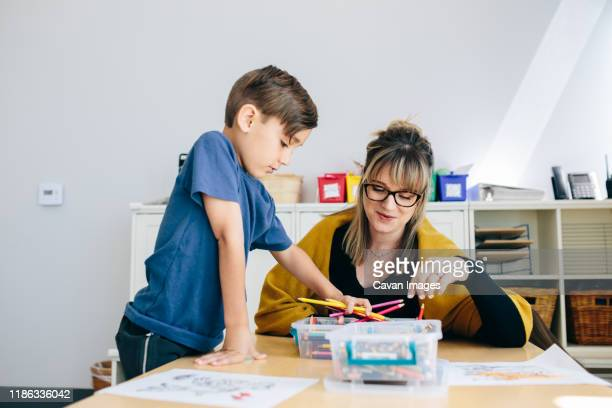 boy grabs colored pencils while teacher sits at table with him - calabasas stock pictures, royalty-free photos & images