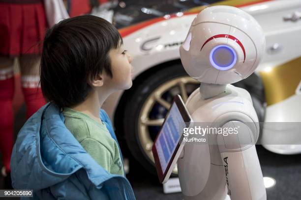 A boy greets to a SoftBanks humanoid robot Pepper during the Tokyo Auto Salon 2018 in Chiba Prefecture on Jan 12 2018