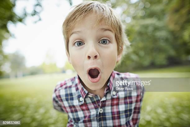 boy grimacing in park, portrait - surprise face kid - fotografias e filmes do acervo