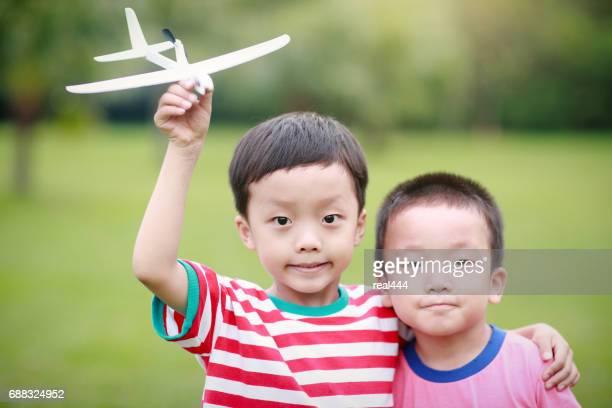 紙飛行機を持っている少年の手