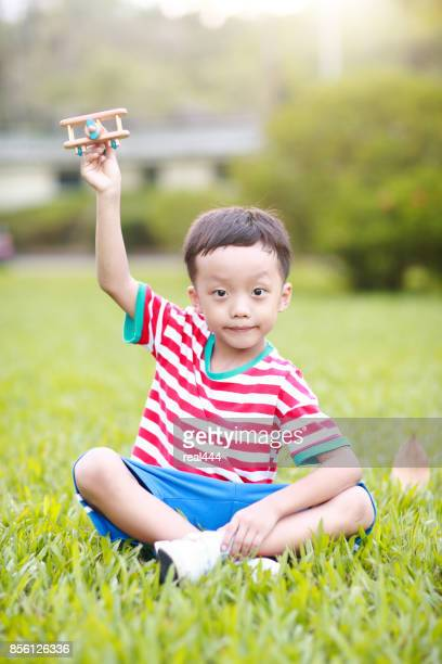 Boy hand holding a paper plane