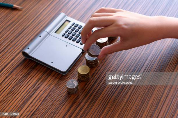 Boy hand Put Coins To Stack Of Coins ,calculations , savings, finances, economy and home concept .