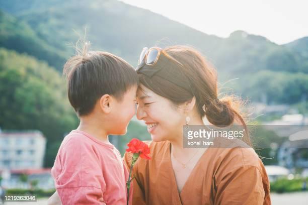 母親にカーネーションの花を手渡す少年 - 母の日 ストックフォトと画像
