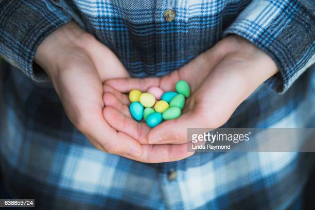 Boy hands holding mini multicolor candy eggs and his hands