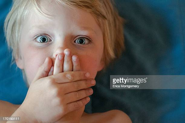 boy (6-8) hands over mouth. surprised expression