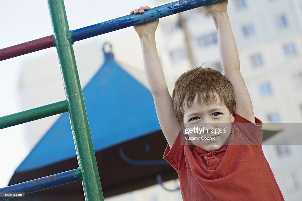 A Boy Hanging From A Playground Bar High-Res Stock Photo ...