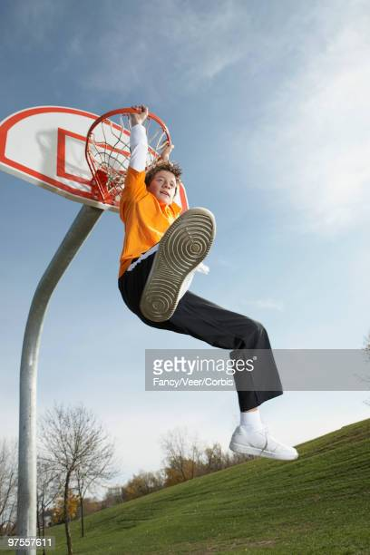 Boy hanging from basketball hoop
