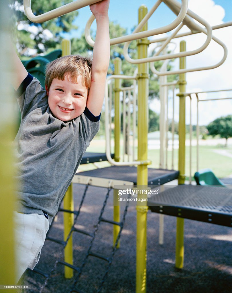 Boy (6-8) hanging from monkey bars in playground, smiling : Stock Photo