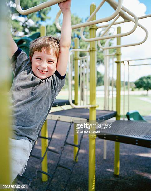 Boy (6-8) hanging from monkey bars in playground, smiling
