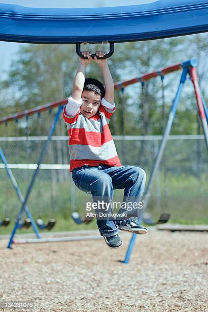 Boy hanging from monkey bars