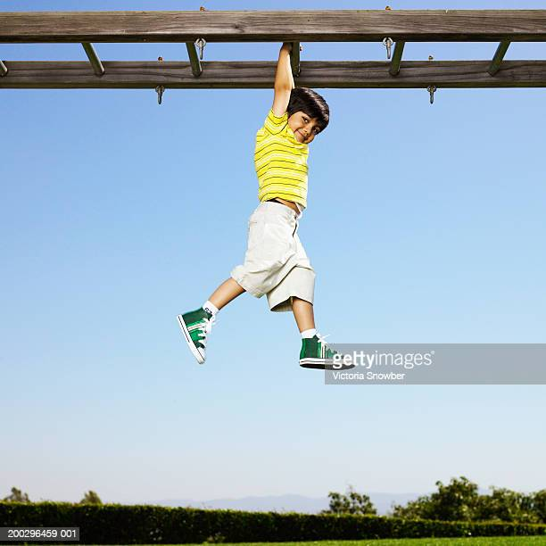 boy (3-5) hanging from monkey bars - monkey shoes stock photos and pictures