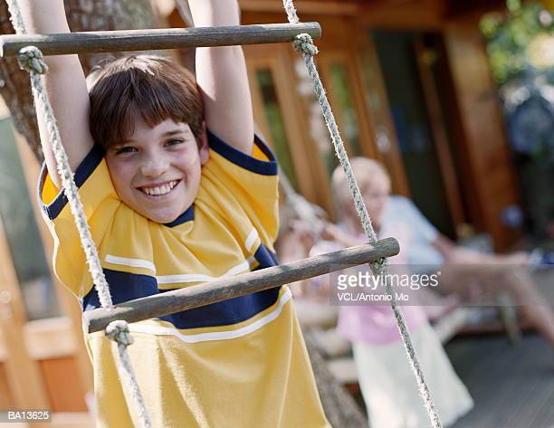 Boy (8-10) hanging from rope ladder, close up, portrait