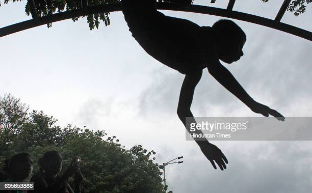 A boy hanging on a climbing frame at Shivaji Park Dadar as monsoon clouds hover in skyline on June 12 2017 in Mumbai India The muchawaited Southwest...