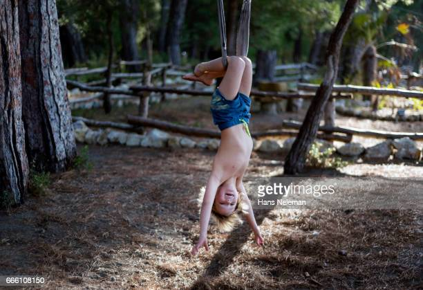 Boy hanging on the rope upside down