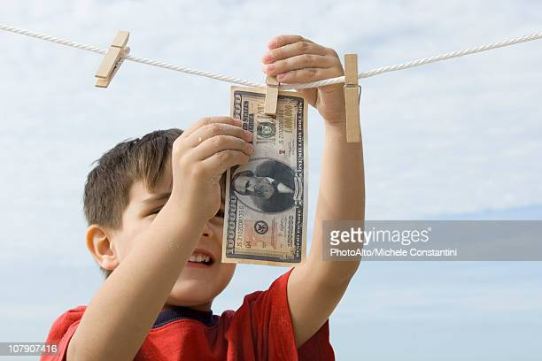 Boy hanging one million dollar bill on clothes-line