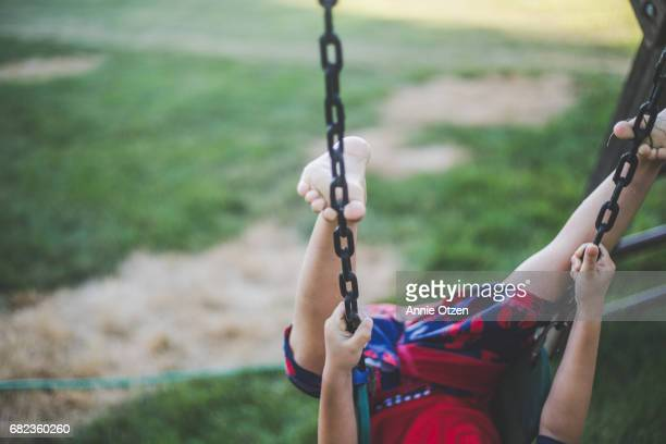 Boy hanging Upside down from swing